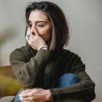 depressed woman sitting in room